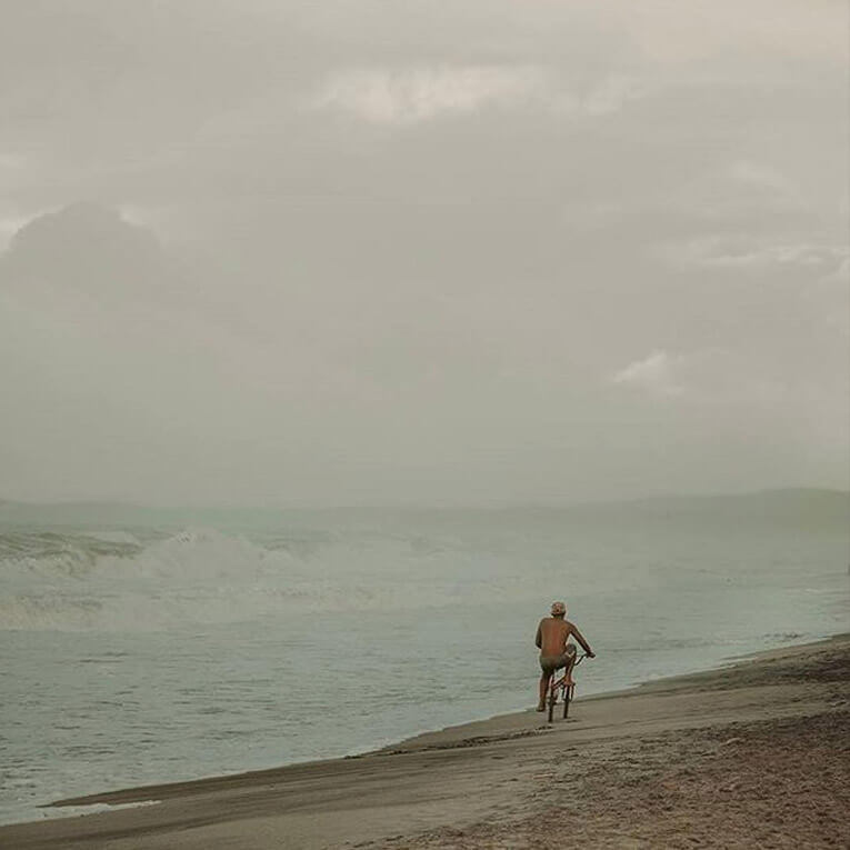 Man traveling by bicycle on the beach